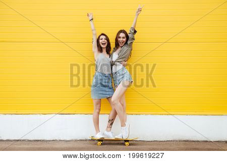 Picture of two young happy women friends standing over yellow wall. Looking at camera.