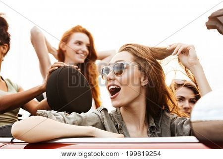 Group of happy young women enjoying a car trip together