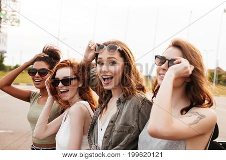 Picture of young amazing women friends in sunglasses standing outdoors.
