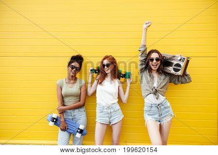 Picture of three young happy women friends standing over yellow wall. Looking at camera holding boombox and skateboards.