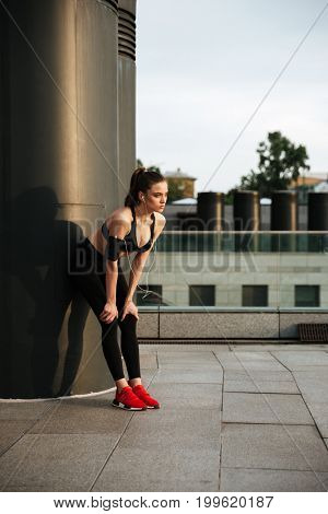 Photo of concentrated young sports lady standing with earphones outdoors and looking aside.