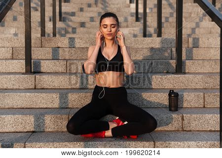 Photo of amazing young sports lady sitting with earphones outdoors and meditate.
