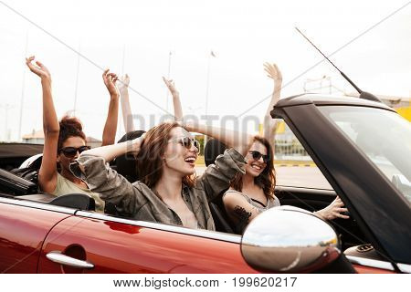 Picture of happy emotional four young women friends sitting in car outdoors.