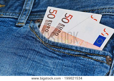 Earnings allowance or benefit concept - fifty euro bank notes in jeans pocket. Jeans are old and worn - poverty or crisis concept. Close up macro capture with blur focus.