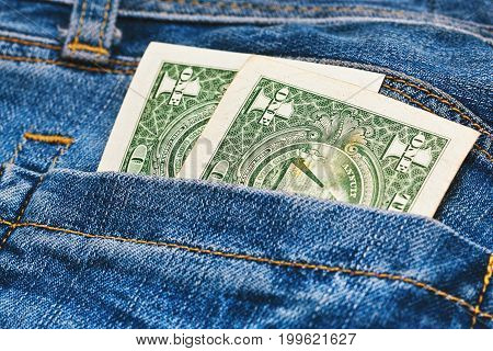 Only two one dollar notes in worn jeans pocket. Close up capture blur focus old banknotes.