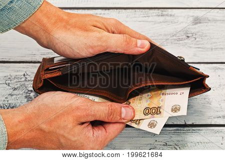 Man in old worn jeans jacket holding in hands almost empty leather wallet with just two hundred russian rubles - around 3 US dollars. Crisis poverty concept.