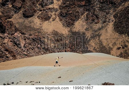 Traveler walks in the valley of the crater of Teide volcano against the mountain Tenerife Canary islands Spain