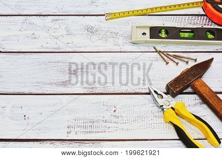 Different hand tools for construction repair wood works - pliers hammer ruler level tool some screws. Tools are used captured on rough wooden background. Top view flay lay.