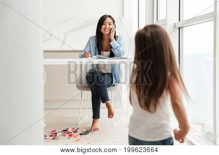 Smiling asian woman talking on a mobile phone and working on laptop while her little daughter playing at home