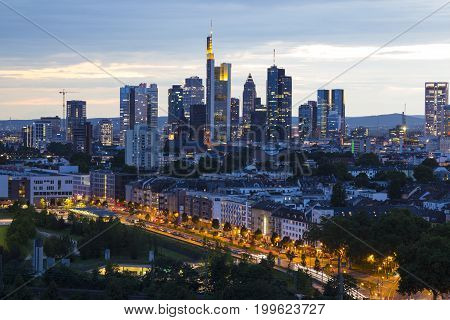 Frankfurt am Main - business capital of Germany at dusk. Top view of the business center: lit skyline buildings and city streets in the night lights.