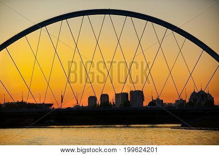 View to the Astana city and bridge over the Ishim river at sunset in Astana, Kazakhstan.