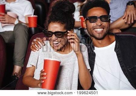Attractive afro american couple watching 3D movie and laughing while sitting in a movie theater