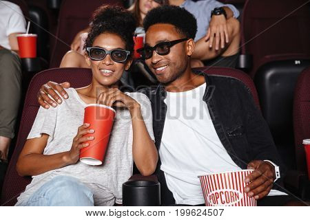 Happy afro american couple watching 3D movie and eating popcorn while sitting in a movie theater