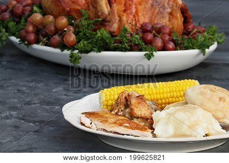 Dinner plate of roasted Thanksgiving turkey mashed potatoes corn on the cob dressing and dinner rolls in front of a whole roasted turkey.