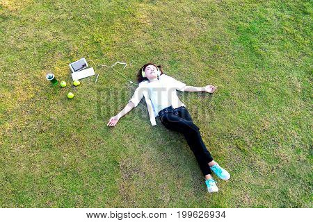 Young women lying in summer grass with headphones listening to music and playing notebook relaxing sunny day greenery tone 2017