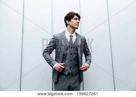 Young businessman in suit and necktie posing isolated against white wall
