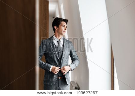 Handsome businessman in suit posing and looking out of the window while standing indoors