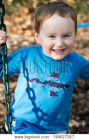 View of Young boy having fun outside at park on a playground swing set