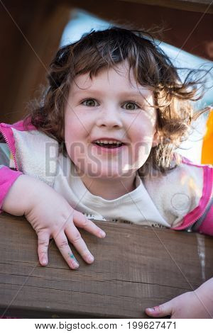 View of Young girl having fun outside at park on a playground swing set
