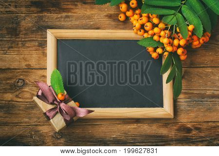 Bunch of rowan branch blackboard in frame gift box on wooden table autumn composition space for text rustic style