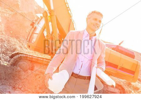 Smiling architect looking away while holding blueprints and hardhat at construction site