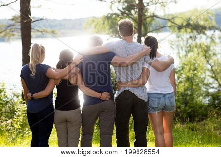 Rear View Of Friends Standing Arms Around In Forest