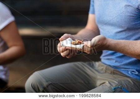 Mature Man Holding Stuffed Bread In Forest