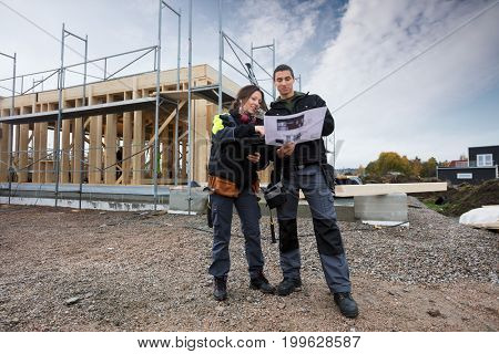 Carpenters Discussing About Plan Against Incomplete Building