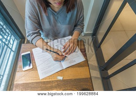 Overhead view of a young woman writing note, doing homework