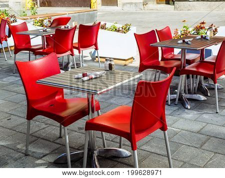 Outdoor patio of a restaurant in urban setting with red chairs