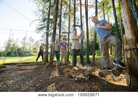 Fit Friends Standing On Swinging Logs In Forest