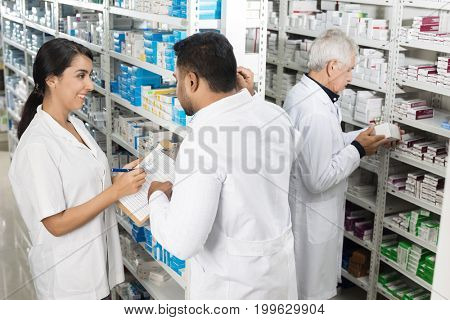 Pharmacists Working By Shelves In Pharmacy