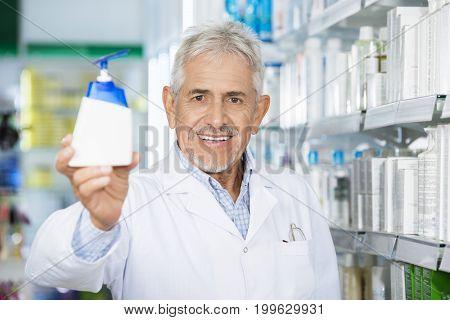 Chemist Holding Soap Dispenser In Pharmacy