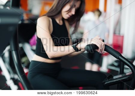 Woman 20s wearing smart watch working out on exercise bike 20s.