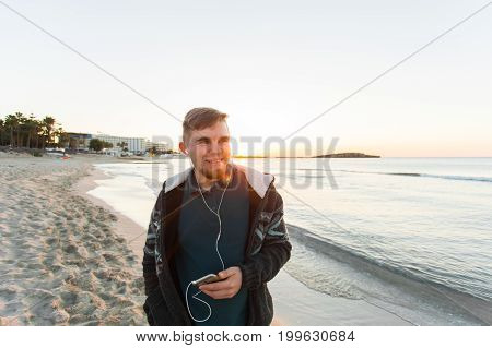 stylish young man in a shirt and shorts and sneakers listening to music in headphones on a smartphone and is sitting on pier looking at sea on yachts boats and the sunset, music lounge , relaxing