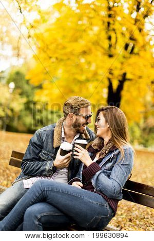 Young Couple Sitting On The Bench With Coffee Cups In The Autumn Park