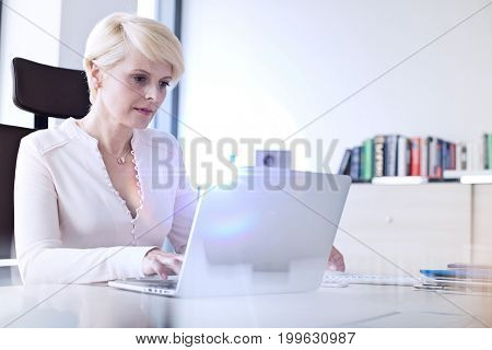 Mature businesswoman using laptop at desk in office