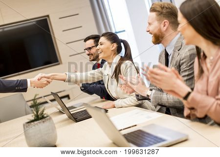 Business people shaking hands finishing up a meeting in modern office