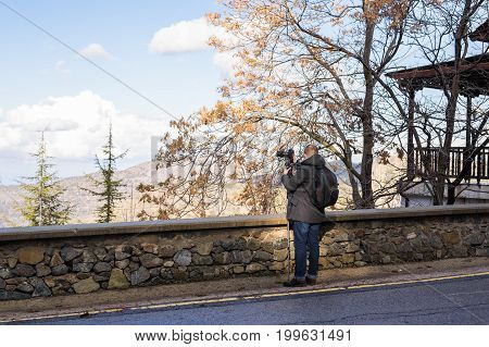 Travel, vacation, photographer and hitchhiker concept - traveler man photographed town.