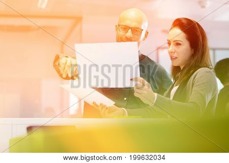 Businesswoman with male colleague discussing over documents in office