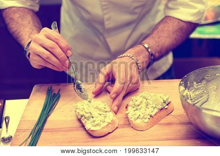 Chef is cooking bruschettas with guacamole avocado sauce, toned image