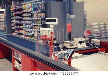 New and modern checkout terminal in a supermarket, nobody, toned image