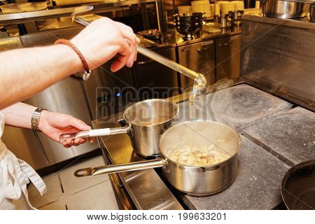 Chef is pouring broth in pot with mushrooms, toned image