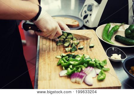Chef is cutting vegetables at commercial kitchen, toned image