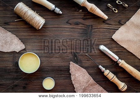 Leather craft. Knife, awl and other tools on dark wooden background top view.