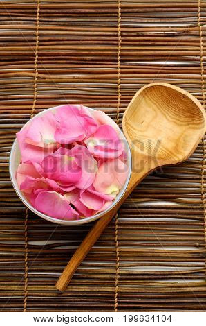 Many pink rose petals in bowl on mat background