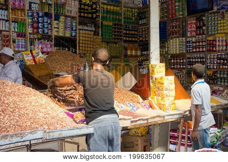 Rissani Morocco - May 09 2017: Shop owner and shop assistants are filling up stock in their shop early morning at the Rissani market in Morocco.