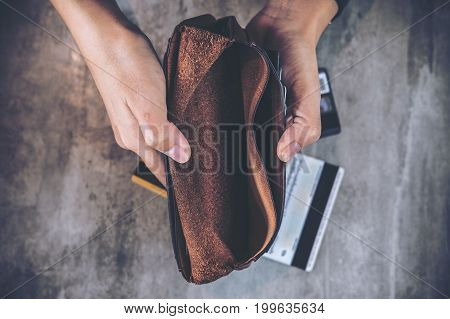 Top view image of a man's hands open an empty leather wallet with credit cards on the table