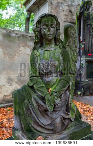 Antique stone staue  of little girl on famous old Olsanske cemetery in Prague, Czech Republic.