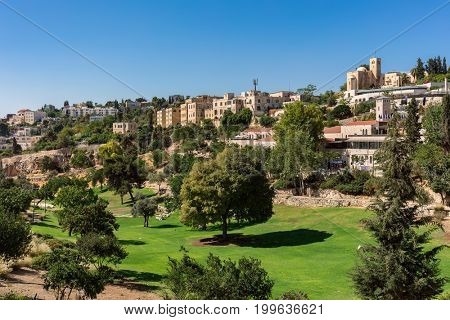 View of green lawn and trees of Zurich Garden as typical houses on background in Jerusalem, Israel.